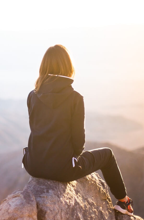 woman sitting on top of a mountain looking at the horizon