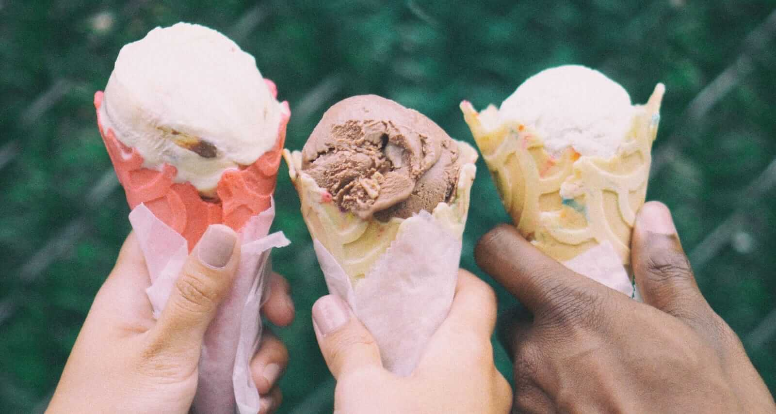 hands holding three cones of ice cream